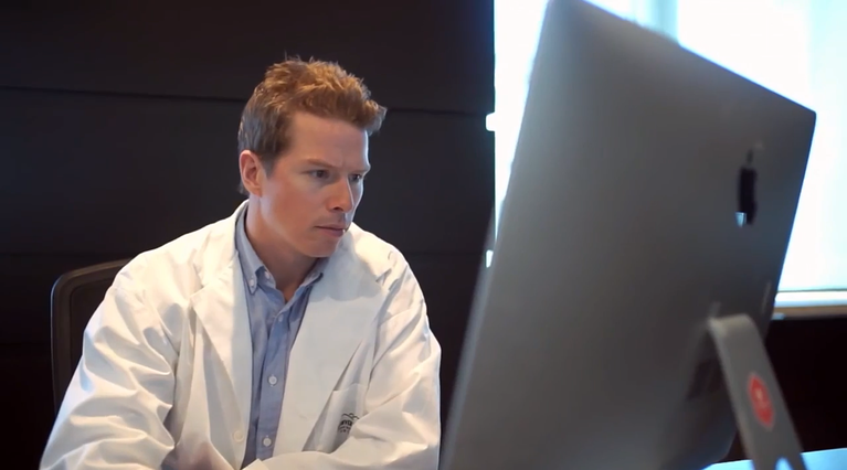Dermatologist Investigating Patient File on DermEngine Intelligent Dermatology Software